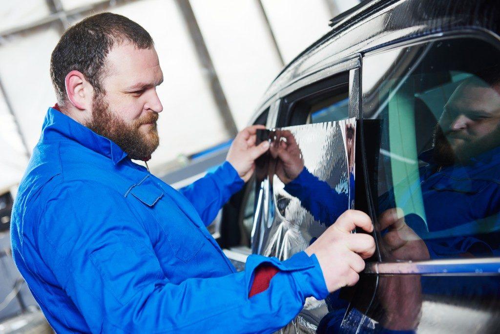 Man applying tint on a car's window