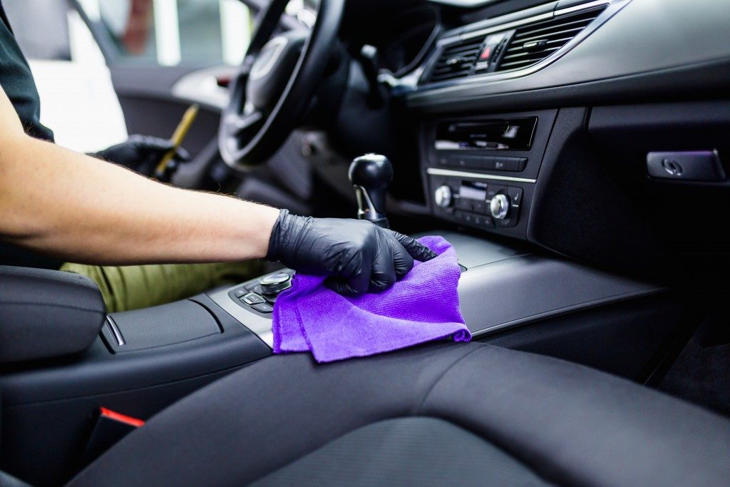 man wiping car dashboard