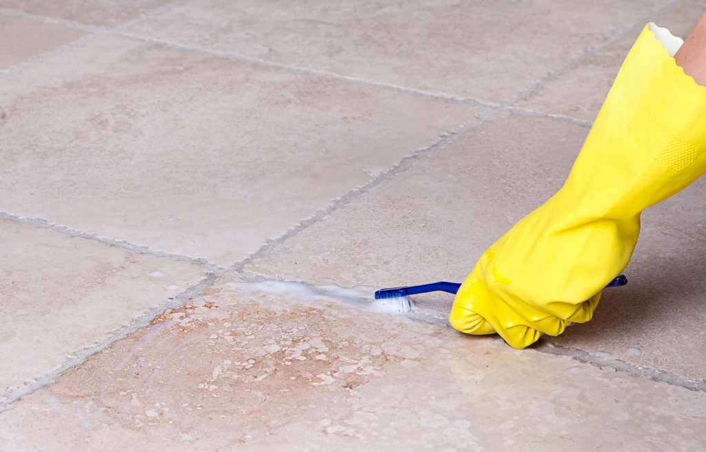 gloved hand cleaning tile grout