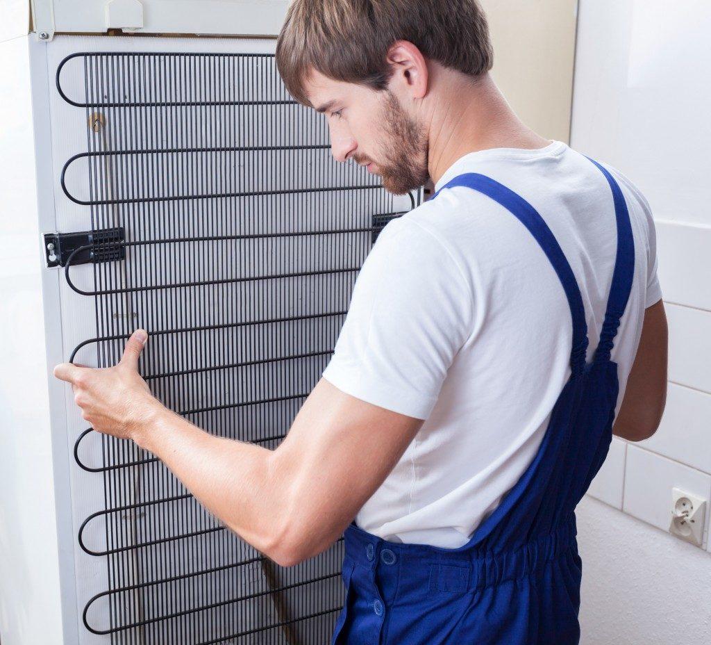 man repairing broken refrigerator