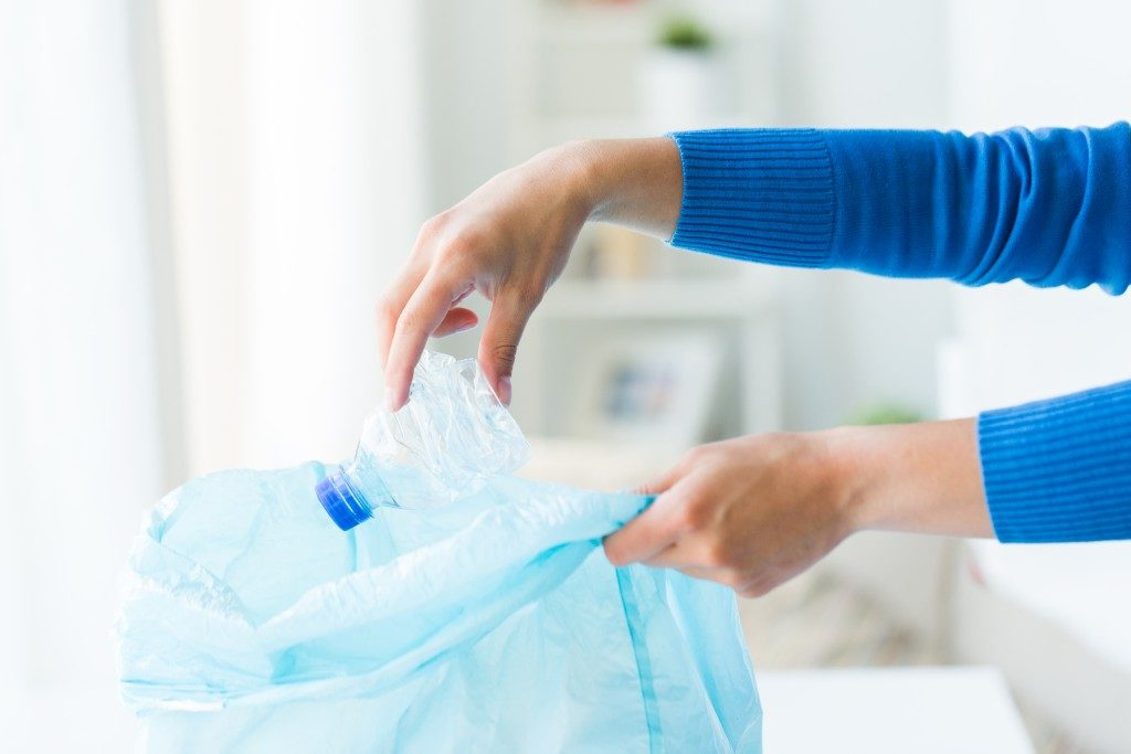 person putting plastic bottle in the trash bag