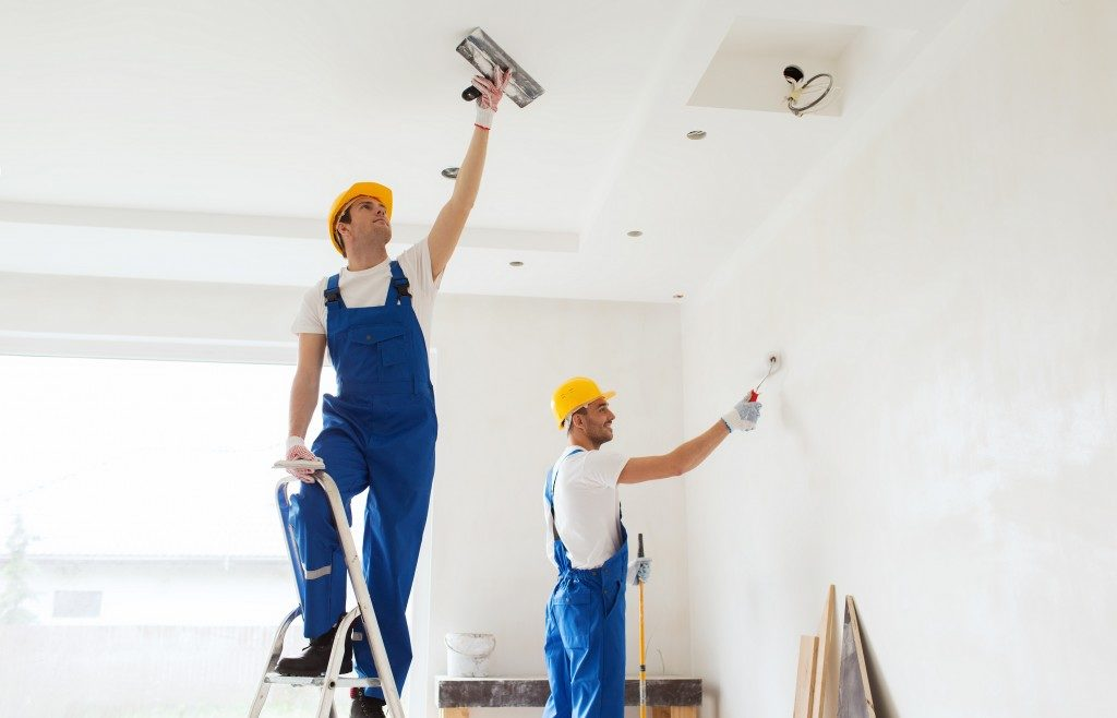 contractors painting the ceilings and walls