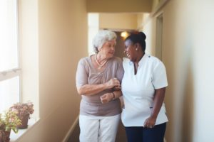 Portrait of happy female caregiver and senior woman walking together at home