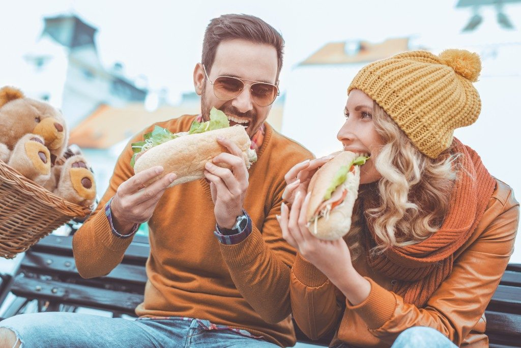 couple eating sandwich while travelling