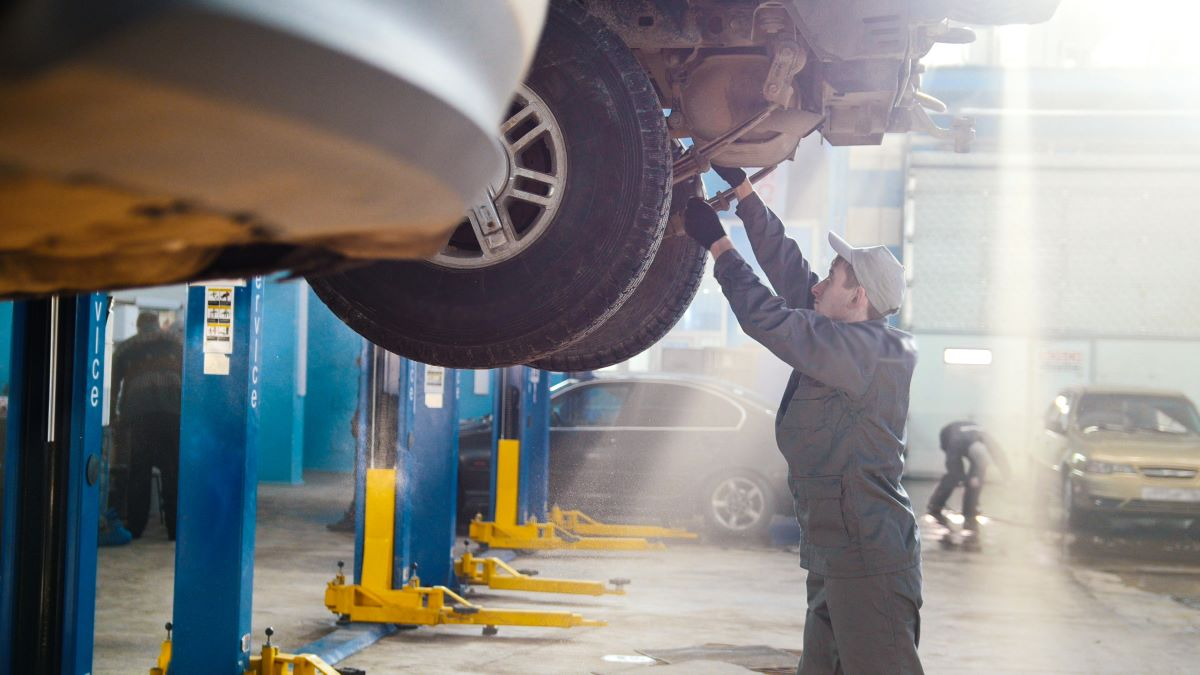 mechanic working on the underside of a car