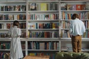 man and woman reading by the bookshelf