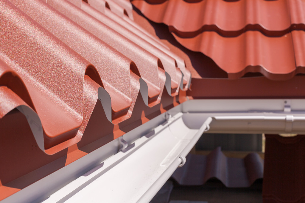 New red metal roofing with white rain gutter