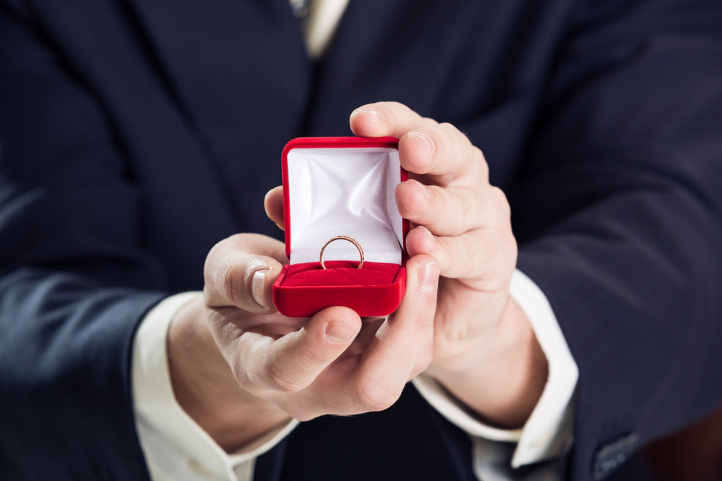 holding wedding ring and gift box
