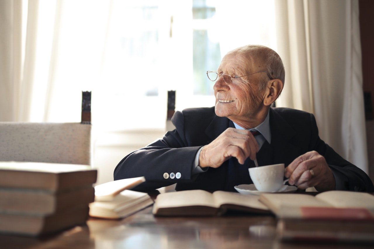 old man reading a book with coffee