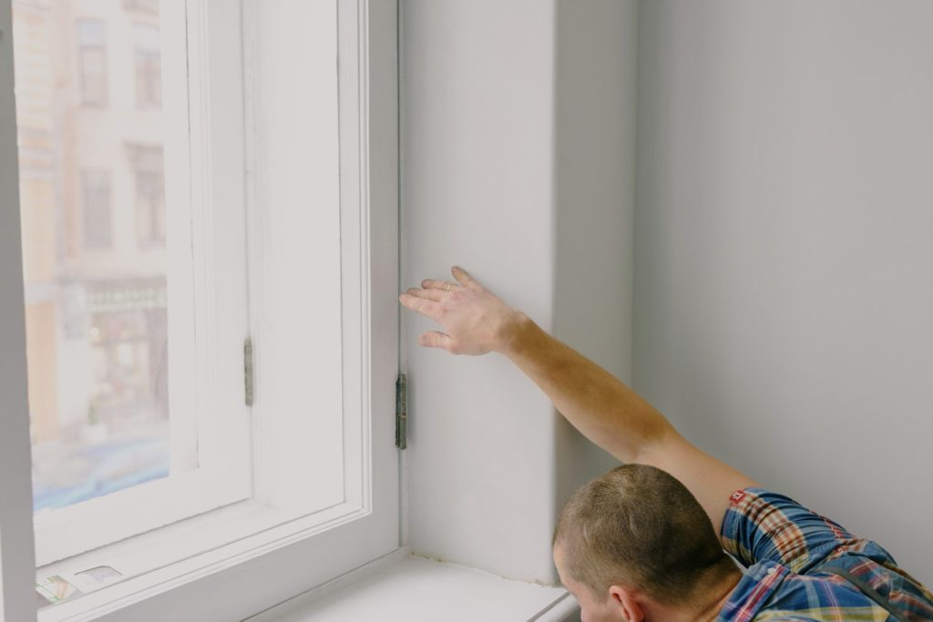 person measuring a window