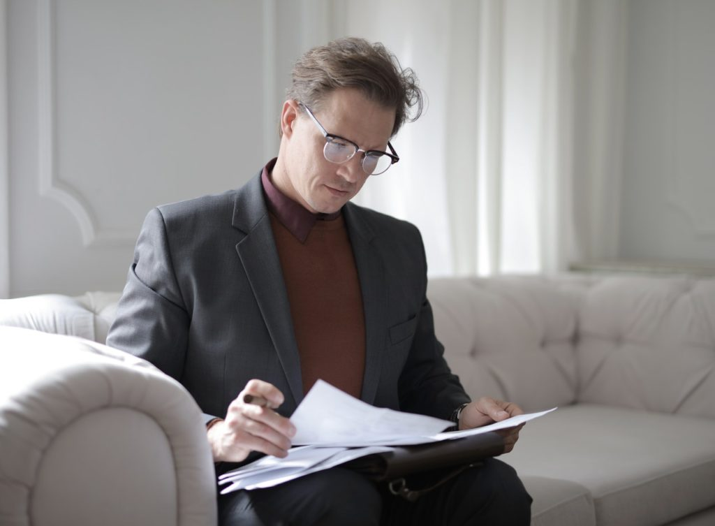 man sitting down holding papers reading