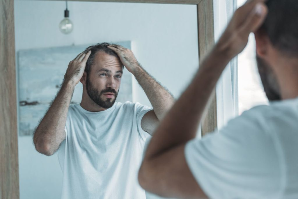 man touching his hair in front of mirror